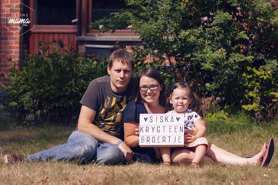 """Man, vrouw en kind met bord dat zegt """"Siska krijgt een broertje"""" om zwangerschap aan te kondigen"""