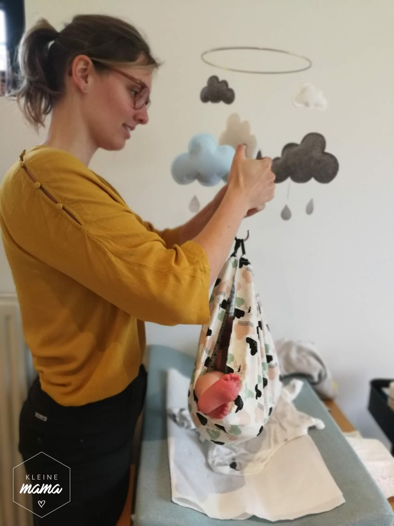 Vroedvrouw weegt baby met weeghaak