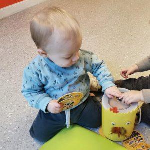 voorbeeld gleufdoos kind stopt kaartje in gele gleufdoos