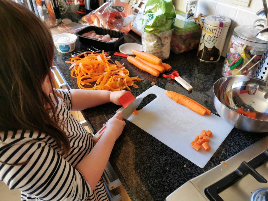 Kleuter snijdt met kindermes in wortel