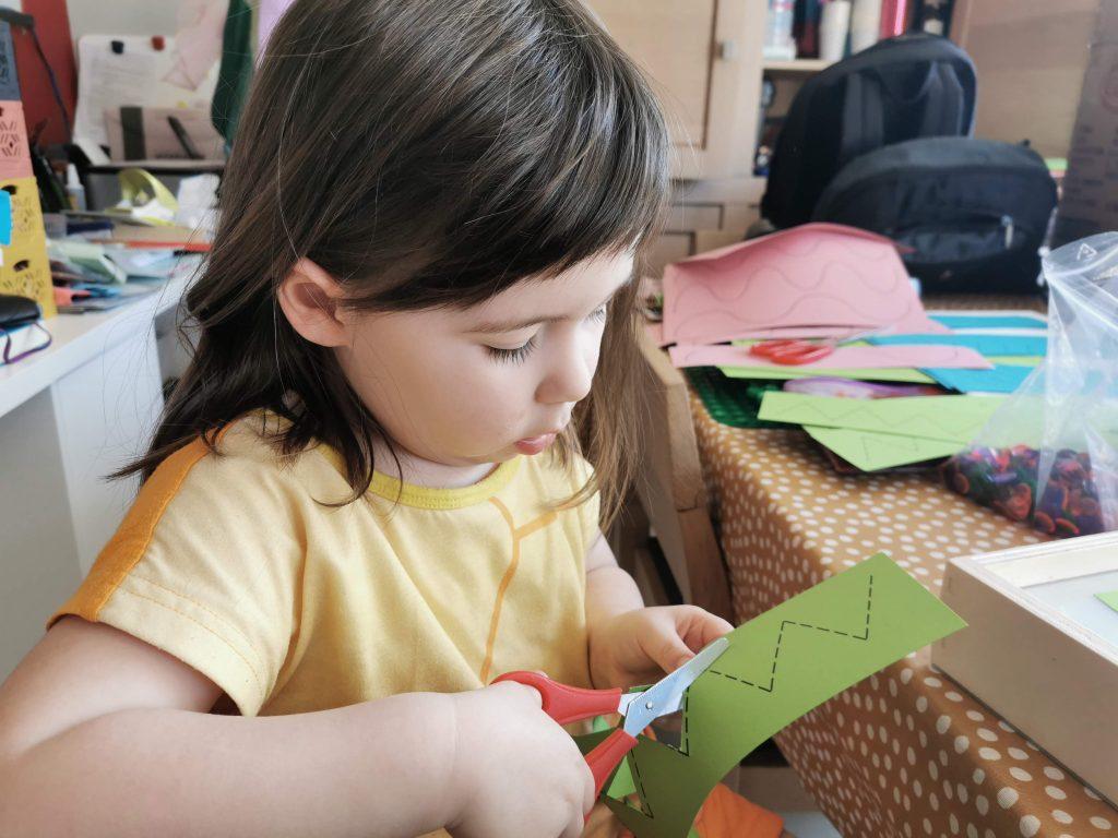 Kleuter knipt met kinderschaar in kaarten